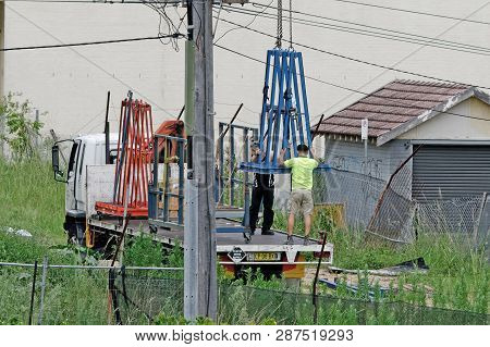 Gosford, New South Wales, Australia - January 31, 2019: Workmen Loading A Materials Cradle Onto Tran