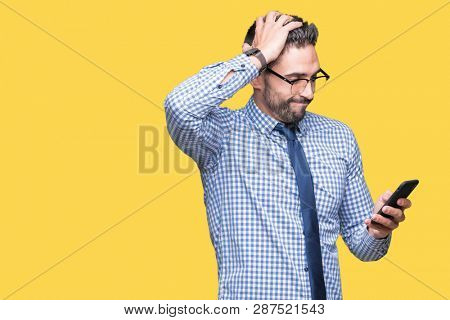 Young business man using smartphone over isolated background stressed with hand on head, shocked with shame and surprise face, angry and frustrated. Fear and upset for mistake.