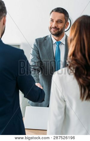 Selective Focus Of Handsome Advisor In Suit Shaking Hands With Investors At Office