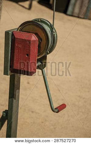 Small Metal Hand Crank For Pulling Steel Cable In A Sunny Day At The Roman Theater Of Merida. Founde