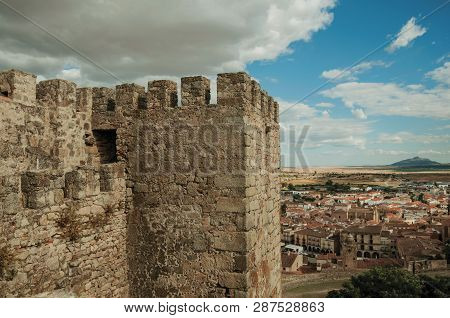 Stone Tower Wall With Crenel, Merlons And Old Buildings Cityscape, Seen From The Castle Of Trujillo.