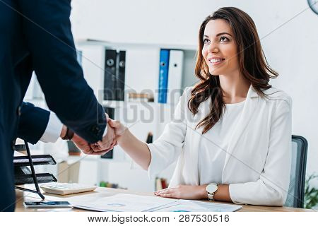 Beautiful And Smiling Advisor And Investor In Suits Shaking Hands At Workplace
