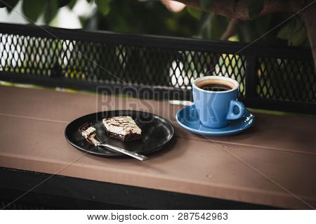Abstract Scene Of Coffee Break Meal Set Including Black Coffee, And Brownie Cheese Cake On Outdoor W