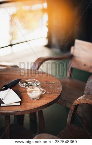 Abstract Scene Of Coffee Cup And Notebooks On Rustic Wood Table. Coffee Break And Relax Time. Workin