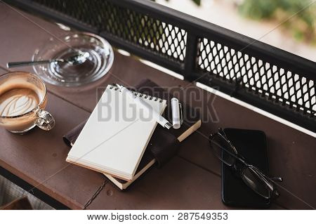 Abstract Scene Of Opened Small Notebook, Pen, Glasses, Mobile Phone, And Coffee Cup On Wood Counter.