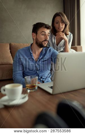 Man and woman enjoying time together browsing on laptop at home