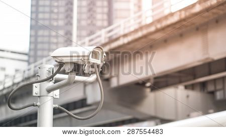 Security Camera Equipment And Traffic Concept - Security Camera Equipment On Pole In Evening Traffic