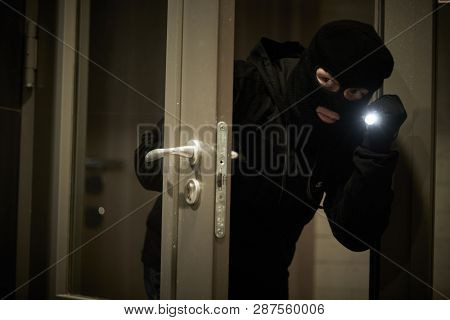 Burglar thief in mask. break-in of an apartment.