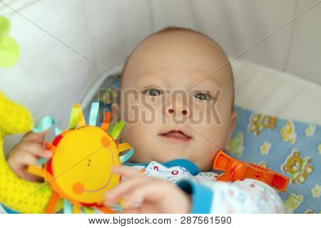 Baby Boy or Girl lying Down in Pram. Cute Child in Baby Carriage