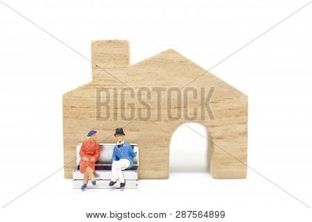 Miniature People :  Husband And Wife Sitting In Front Of House On White Background