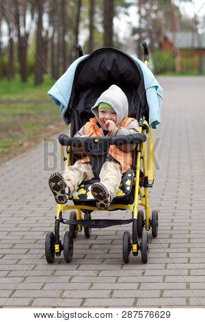 Baby Boy or Girl Sitting in Pram. Cute Child in Baby Carriage