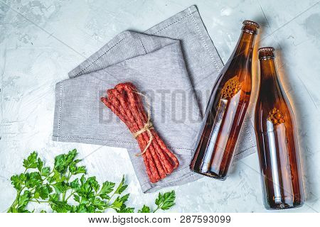 Craft Beer With Sausages Kabanosi And Green Parslye On Gray Concrete Surface Background, Copy Space