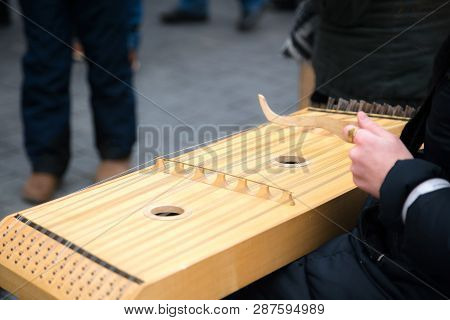 Girl Performing Music With Traditional String Instrument At The Fare On The Street