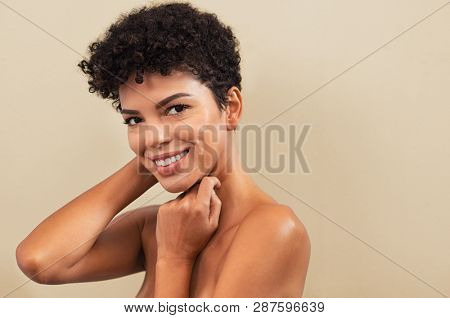 Beautiful young woman touching her face skin and feel the softness with copy space. Smiling brazilian girl feeling skin face after beauty treatment. Portrait of african woman looking at camera.
