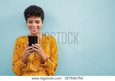 Happy smiling black woman using smart phone. Young brazilian woman writing a message with mobile isolated on blue background. Portrait of african american stylish girl using cellphone with copy space.