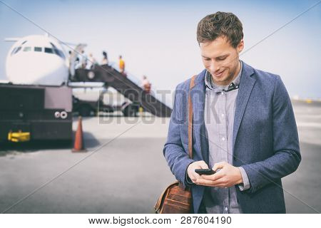 Man texting on phone leaving for business trip at airport . Happy businessman on smartphone boarding plane. Young male professional using 5g data on smartphone app in flight flying wearing blazer.