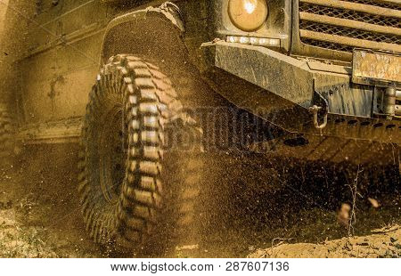 Off-road Vehicle Goes On Mountain Way. Bottom View To Big Offroad Car Wheel On Country Road And Moun