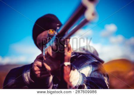 Hunter Aiming Rifle In Forest. Hunter With Shotgun Gun On Hunt. Autumn Hunting Season. Barrel Of A G