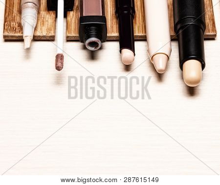 Various Makeup Concealers On Light Wood Table. Make-up Correctors. Close-up, Copy Space