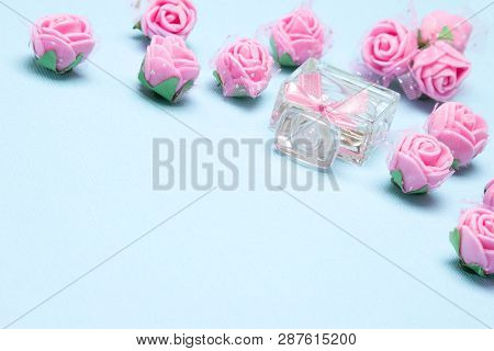 Perfume Bottle With Small Pink Roses And Bow. Blue Background With Copy Space