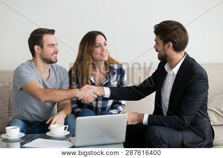 Happy Family Couple Renters Tenants Handshaking Realtor Landlord At Meeting