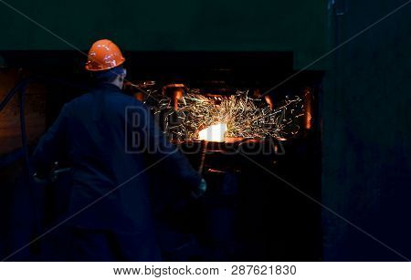 Hot Metal Ingot Being Loaded Into A Hammer Forge. Worker Forges Iron Products. Hot Iron In Smeltery