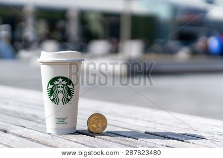 Cryptocurrency Bitcoin Next To Starbucks Cup. Starbucks Adoption Of Blockchain Concept - Slovenia -