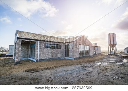 New Brick House At A Construction Site With A Large Silo In The Morning