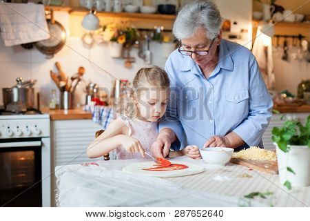 Kid And Grandmother Are Cooking Italian Pizza In Cozy Home Kitchen For Family Dinner. Cute Girl Is H