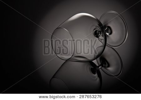 Silhouette of empty snifter glass (brandy snifter, brandy bowl, cognac glass, or balloon) on a black background with reflection. Glassware for aged brown spirits. Contour with gradient and highlights