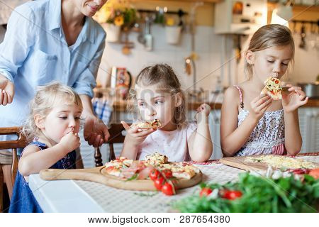 Children Are Eating And Tasting Italian Homemade Pizza Cooking Themselves Together. Cute Kids Are En