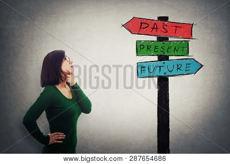 Pensive Businesswoman Thinking Looking Up At A Signpost With Arrows Showing Past, Present And Future