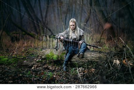 Mad Furious Viking Woman Warrior With A Sword In Her Hands, In The Woods. Authentic Recreation Of No