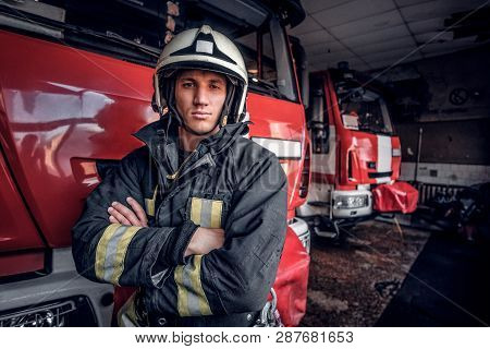 Confident Fireman Wearing Protective Uniform Standing Next To A Fire Engine In A Garage Of A Fire De