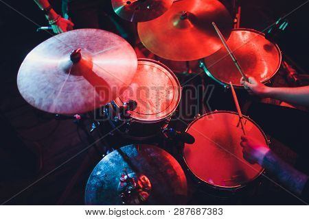 Drummer Playing Drum Set At Concert On Stage. Music Show. Bright Scene Lighting In Club, Drum Sticks