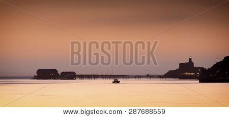 Daybreak And High Tide Around Mumbles Pier In Swansea, South Wales, Uk