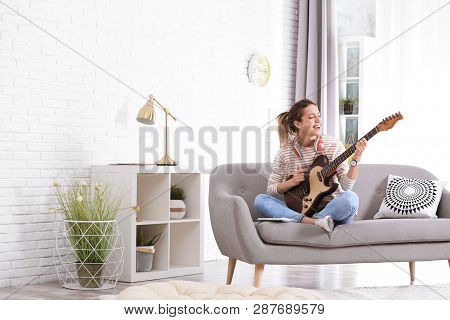 Young Woman With Headphones Playing Electric Guitar In Living Room. Space For Text
