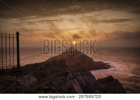 The Sun Emerging To Light Up The Clouds At Daybreak Over Mumbles Lighthouse In Swansea, South Wales,