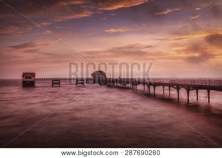 High Tide At Dawn In The Mumbles Area Of Swansea, South Wales Uk, Showing Mumbles Pier And Lifeboat