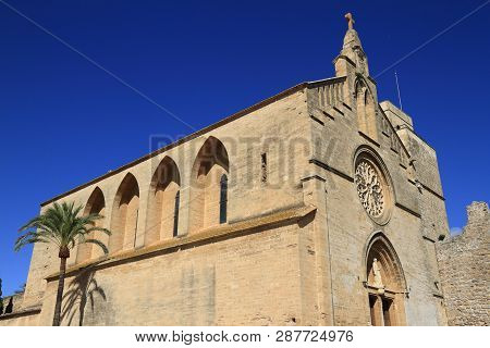 Sant Jaume Cathedral Near Roman Castle Wall In Alcudia,  Mallorca, Balearic Islands, Spain