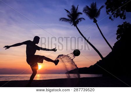 Silhouette Volley Kick Football On The Beach, Asian Man Play Soccer At Sunrise Early Morning.