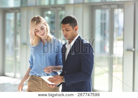 Front view of young diverse business people discussing over digital tablet in office lobby