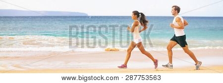 Run fit couple running together on beach banner panoramic background. Two fitness athlete jogging - summer active lifestyle.