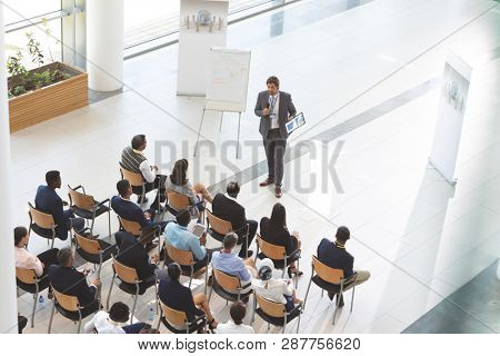 High angle view of male caucasian speaker with digital tablet speaks with microphone in a business seminar with diverse business people  sitting on chair in foreground in conference
