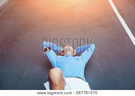 Runner standing on the street near brick wall and checking workout time, armband with mobile phone and earphones with motivating music poster