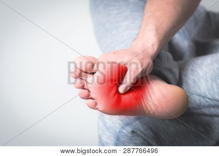 Causian Man Holds Hands To His Painful Feet, Pain In Foot. Red Color Is Area Of Pain