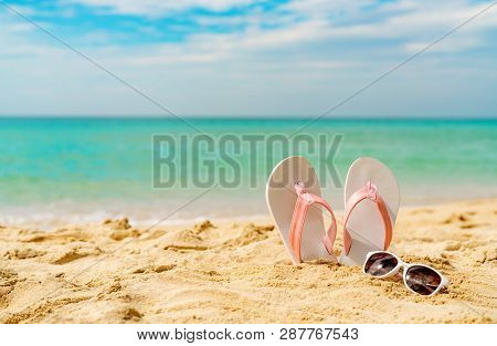 Pink And White Sandals, Sunglasses On Sand Beach At Seaside. Casual Fashion Style Flipflop And Glass