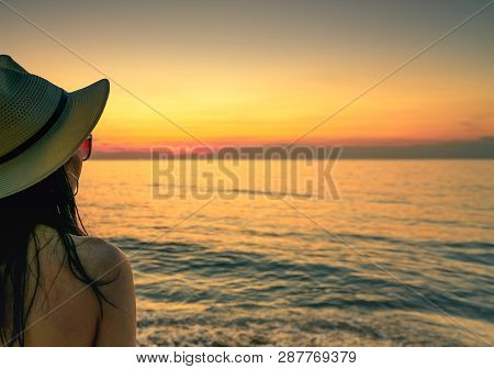 Back View Of Sexy Woman Watching Sunset At The Beach. Woman Wear Sunglasses And Straw Hat Relaxing A