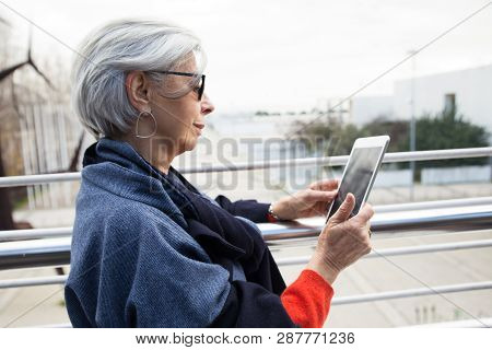Pensive Lady In Sunglasses Using Tablet Outdoors. Side View Of Grey Haired Senior Woman In Casual Br