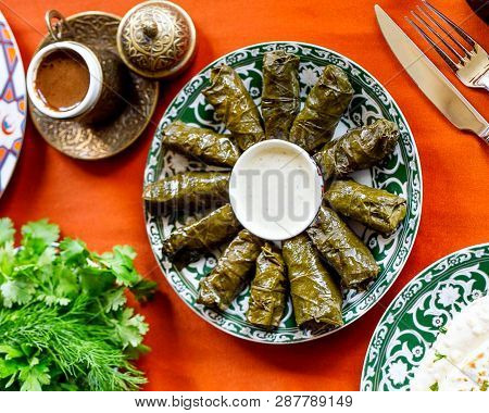 Delicious Dolma Stuffed Grape Leaves & Rice Parsley Cliantro White Sauce. Lebanese Dolma Sarma On Pl